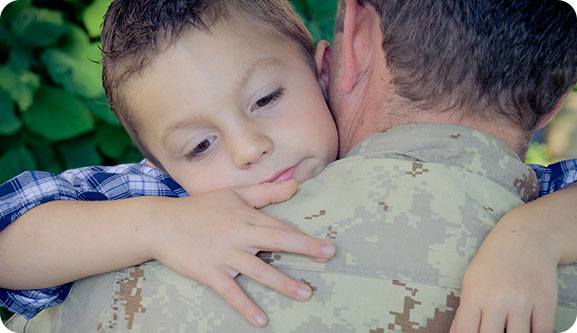 An image of a small child hugging an man in Canadian Armed Forces fatigues