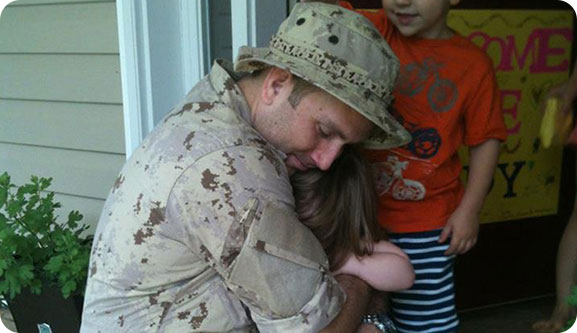 An image of a man in Canadian Armed Forces uniform hugging a small child