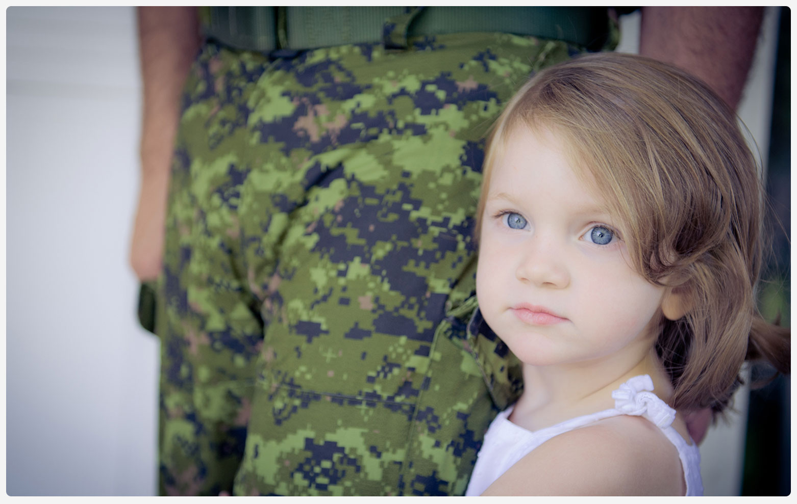 An image of a young girl beside a man in military fatigues