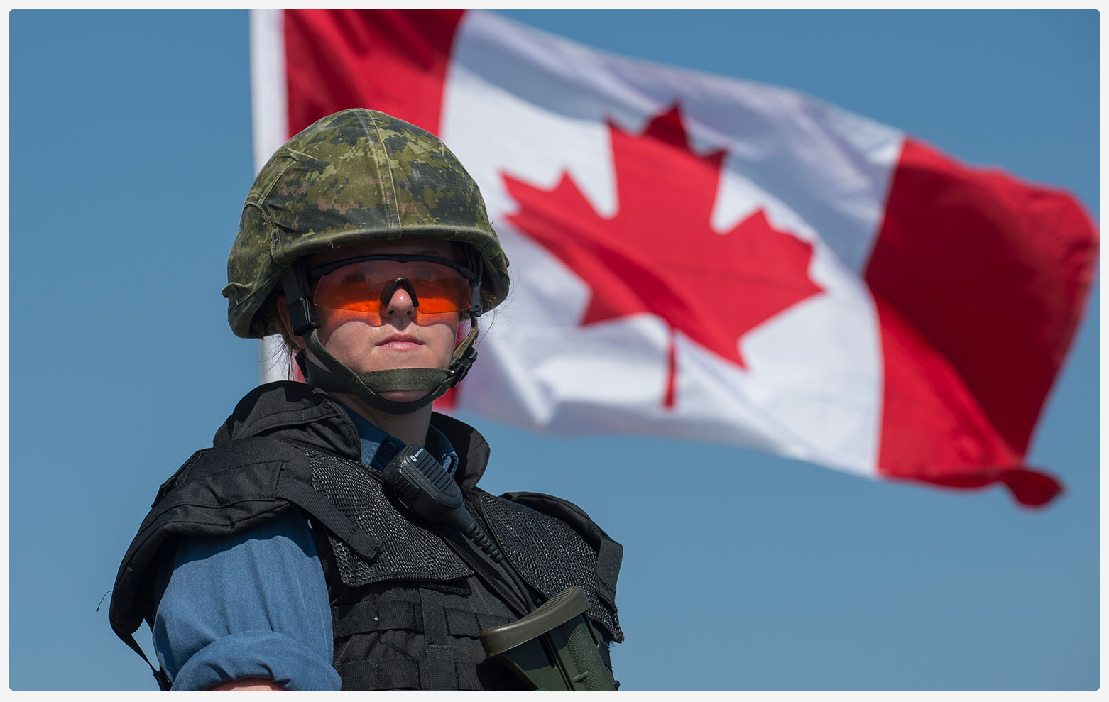 An image of a CAF member standing in front of the Canadian Flag