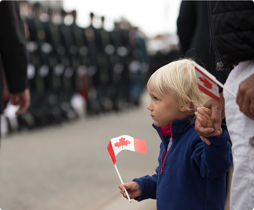 An image of a small child holding a Canadian flag, with soldiers in a blurred background