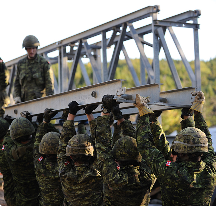 A group of CAF members working together to carry a large metal beam
