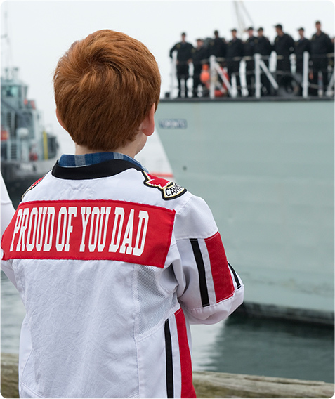 "An image of a young boy with a shirt that says ""Proud of you Dad"" on the back"